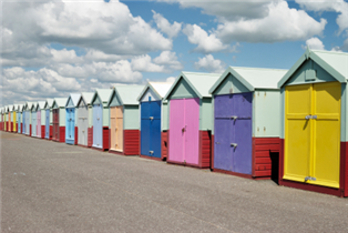 Photograph of a row of colourful beach-huts in Brighton