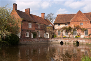 Photograph of several traditional houses by a river in Essex